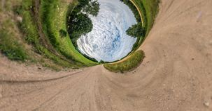 Curvature of space of little planet transformation. Abstract torsion and spinning of full flyby panorama landscape on gravel road. Before storm with awesome stock video