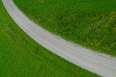 Curve. Road with a curve crossing the green meadow royalty free stock images