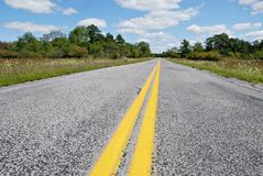 Curve Ahead. Road with yellow lines in rural area Royalty Free Stock Photography