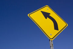 Curve ahead. Road sign on blue sky stock photo