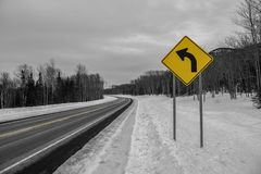 Curve ahead road sign on winter highway. Color splash photo of curve ahead road sign on winter highway royalty free stock photos