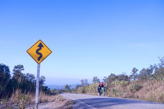 Curve ahead traffic sign. On blue sky with people riding motorcycle royalty free stock images