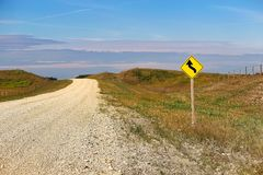 A curve ahead warning sign beside a country road.  stock images