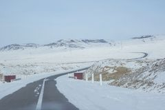 Curve asphalt road surrounding by snow near Lake Khovsgol at Mongolia Royalty Free Stock Photos