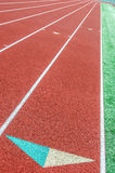Curve on a athletics running track. An empty red athletics track / race track in a green field at a school royalty free stock image