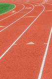 Curve on a athletics running track. An empty red athletics track / race track in a green field at a school stock images