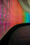 Curve Of Colors. A curved wall of glass is beautifully illuminated with bright and happy shades of colors royalty free stock photography