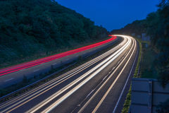 Curve of commuter traffic. Headlights and Tail lights of commuter traffic on a summers evening on motorway in Devon, UK royalty free stock photo