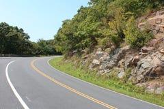 Curve en el camino que desaparece alrededor de una pared de la roca y de árboles Foto de archivo libre de regalías
