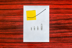 Curve graph printed on a sheet of paper and yellow note with arr Royalty Free Stock Photos
