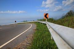 Curve la señal de tráfico en abajo fondo del cielo azul de la colina Fotos de archivo libres de regalías