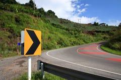 Curve la señal de tráfico en abajo fondo del cielo azul de la colina Foto de archivo