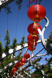Curve Of Lanterns. A lovely curve of red chinese lanterns. Part of a Buddha's Birthday celebrations. Purple Bouganvillea flowers. Location: Brisbane, Queensland stock images