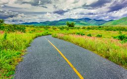 Curve line country road through the medow and mountain range wit. H overcast sky stock photos