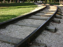 Curve in railroad tracks with grass stock images