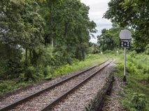 Curve railway line with the traffic signal pole. Curve railway line with the traffic signal pole in the tropical forest of Thailand royalty free stock photo