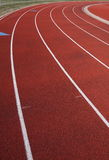 Curve of a red running track. Lanes of a red running track royalty free stock photos