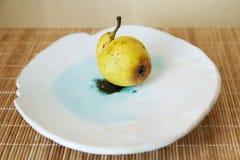 Curve ripe pear on a ceramic plate. Curve ripe pear lying on a ceramic plate Stock Images
