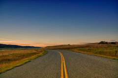 Curve in the Road at Dusk. Landscape of a curved country road at sunset Royalty Free Stock Photography