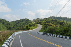 Curve of road and green field in country at nan thailand Stock Photos