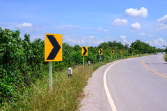 Curve road and right tuning sign with blue sky Stock Photography