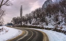 Curve road on serpentine in winter. Dangerous turnaround on slippery slope early in the morning Stock Images
