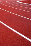 Curve of a running track. Close to the ground perspective of an oval running track with artificial surface...white lane markers Royalty Free Stock Photos