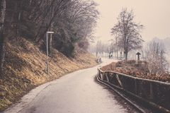 Curve way to turn right with tree line in Bled. Curve way to turn right around mountain with green tree line and brown fence in Bled at Slovenia, Evergreen tree stock photos