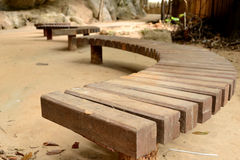Curve Wooden Bench. Brown Curve Wooden Modern Bench in the park royalty free stock image