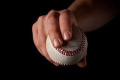 Curveball Grip. A man holds a used baseball with a curveball grip for a pitcher. Black background Stock Image