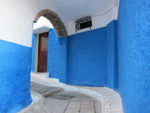 Curved alley with blue walls Royalty Free Stock Photo