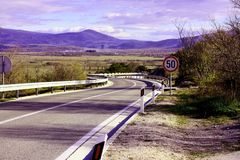 Curved asphalt road going to Drniš, Croatia. Curved road going downhill. South entrance to Drni Royalty Free Stock Photography