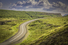 Curved asphalt road in high mountains of Iceland Stock Images