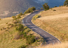Winding mountain road at beautiful sunset. Curved asphalt road in mountain landscape at idyllic sun setting mood stock photography