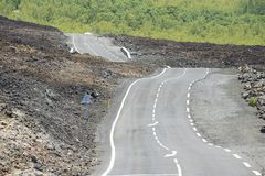 Curved asphalt road over volcanic lava, Reunion island, France. Stock Photos