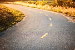 Curved asphalt road in sunset Royalty Free Stock Images