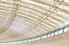 Curved big shoppimg mall roof indoors. Modern metal and glass ceiling contruction stock image