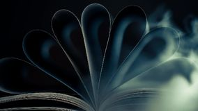 Curved book pages in smoke stock footage