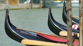 Curved bows of black gondola boats on Grand Canal, romantic atmosphere, Venice. Stock footage stock footage
