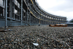 Curved building undergoing construction. Low angle view from ground level of the front facade of a curved building undergoing construction or renovation with royalty free stock photo