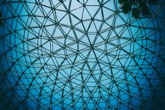 Curved ceiling of dome steel structure with blue sky background. Curved ceiling of dome with geometric frame structure in black steel. modern and contemporary royalty free stock photography