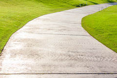 The curved cement pathway through in green golf course. Royalty Free Stock Image