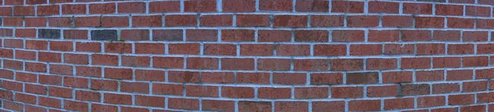 Panorama of rounded brick wall. Curved and centered patterned red bricks in vertical wall. Concavely stretched with white mortar and black bricks stock photography