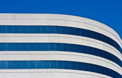A curved concrete and blue glass office building Royalty Free Stock Photography