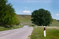 Curved country road lane with bright skies royalty free stock image