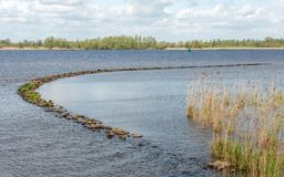Curved dam of basalt boulders in the water of a river. Curved dam of basalt boulders in the water of a Dutch river. The photo was taken on a sunny day in the Royalty Free Stock Image