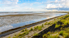 Curved dike at a Dutch estuary Stock Image