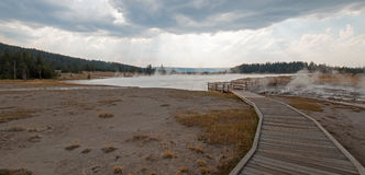 Curved Elevated wooden boardwalk going past Black Warrior Hot Springs and Tangled Creek into Hot Lake in Yellowstone National Park Stock Photo