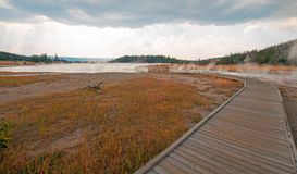 Curved Elevated wooden boardwalk going past Black Warrior Hot Springs and Tangled Creek into Hot Lake in Yellowstone National Park Royalty Free Stock Photography