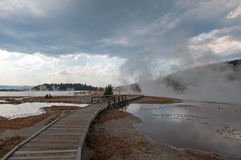 Curved Elevated wooden boardwalk going past Black Warrior Hot Springs and Tangled Creek into Hot Lake in Yellowstone National Park Stock Photos